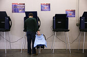 A man carries his baby as he casts his ballot at a polling station at Crossroads Fire Station February 20 2016 in Chapin South Carolina Residents of...