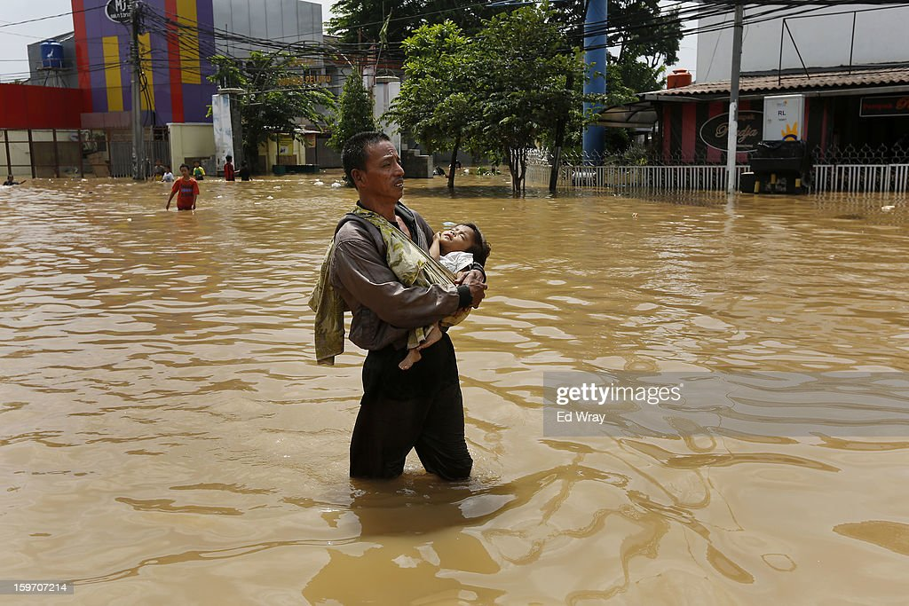 A man carries his baby through floodwaters on January 19, 2013 in Jakarta, Indonesia. Floodwaters receded today after three days of heavy flooding which left thousands of people's homes underwater. According to Indonesian police the death toll has reached 15.