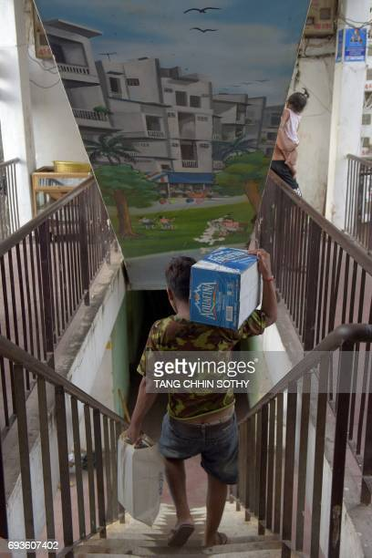 A man carries his belongings as he leaves the residential complex known as White Building in Phnom Penh on June 8 after agreeing to a compensation...