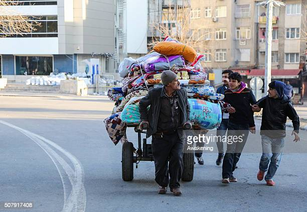 A man carries his belongings ouf of the red zone area during a short break in the curfew on February 1 2016 in Diyarbakir Turkey Parts of Diyarbakir...