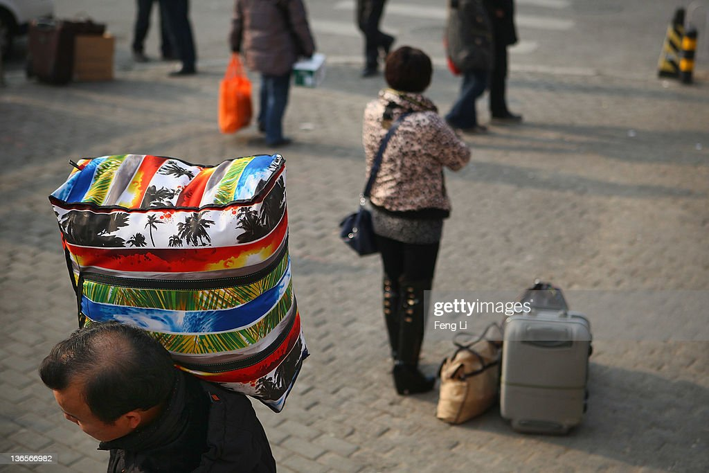 A man carries his belongings to Beijing West Railway Station on January 8, 2012 in Beijing, China. China's annual Spring Festival travel rush begins on Sunday, and authorities estimate 3.158 billion passenger journeys will be made for the Chinese lunar new year during the 40-day travel period.
