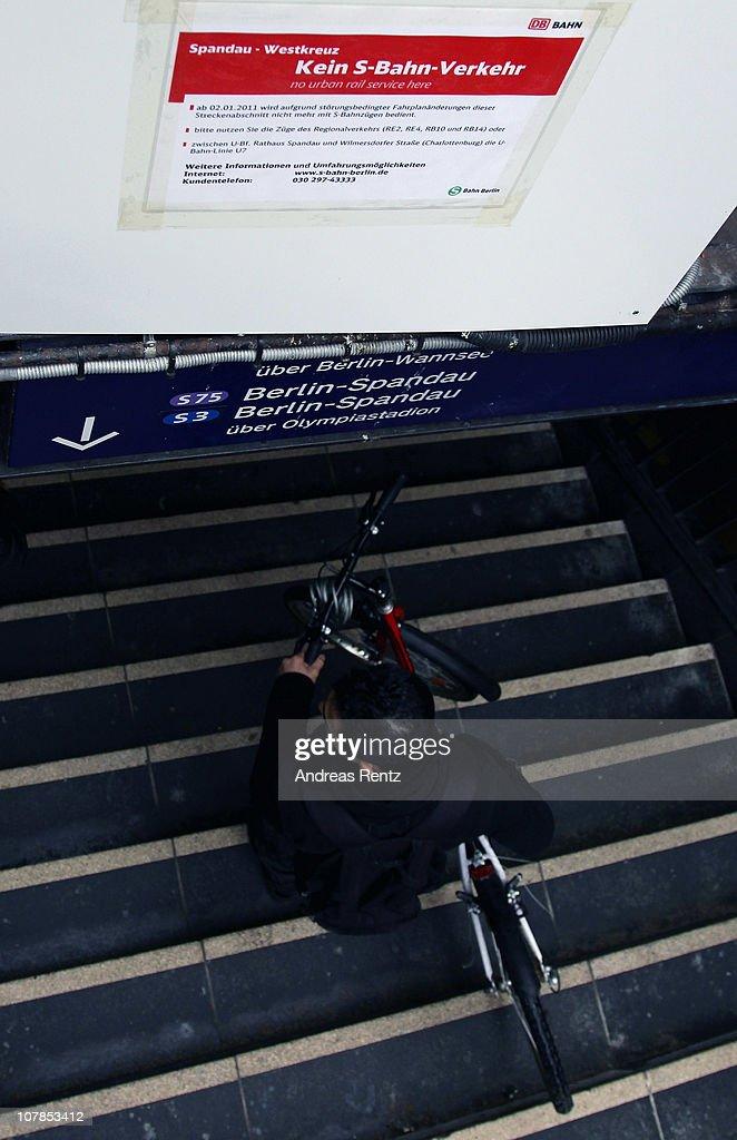 A man carries his bicycle down the stairs as he past a sign that shows the cancellation of service at the Westkreuz station of the Berlin S-Bahn commuter rail network on January 3, 2011 in Berlin, Germany. According to media reports out of the S-Bahn's 1,100 train cars only 426 are in service. The others, according to S-Bahn officials, are in repair due to damage caused by the early and harsh winter weather this year. The shortfall in operating trains has led to longer waits for commuters and, in some cases, cancelled service altogether. The Berlin S-Bahn, a subsidiary of the German state rail carrier Deutsche Bahn, has been unable to keep its full fleet of trains operational for the last two years.