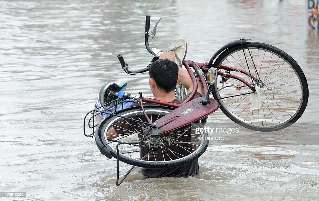 A man carries his bicycle over floodwaters in the farming town of Novaleta, some 26 kilometres outside Manila on August 19, 2013. Torrential rain paralysed large parts of the Philippine capital on August 19 as neck-deep water swept through homes, while floods in northern farming areas claimed at least one life. AFP PHOTO / Jay DIRECTO
