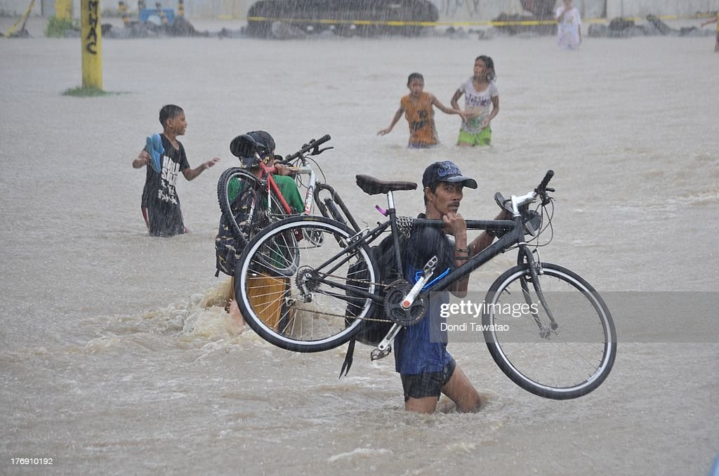 A man carries his bicycle while wading through floodwaters that inundated parts of Las Pinas on August 19, 2013 in Las Pinas City south of Manila, Philippines. Tropical storm Trami which was enhanced by monsoon rains swept overnight through the southern metropolitan cities of Manila and leaving huge parts of four provinces underwater forcing residents to evacuate their homes and seek shelter in evacuation centers. At least three fatalities were recorded with thousands more still needing to be rescued.
