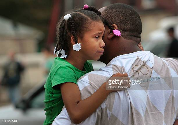 A man carries his crying daughter away from a Boston Market fast food restaurant after antiG20 Summit protestors smashed its windows September 24...