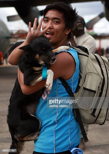 A man carries his dog waves his hand as he walk to board a South Korean cargo plane to evacuate following the recent super typhoon on November 19...