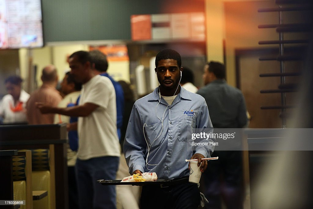 A man carries his lunch inside of a Burger King as employees and supporters demonstrate outside to demand higher pay and the right to form a union on August 29, 2013 in New York City. Across the country thousands of low-wage workers are expected to walk off their jobs Thursday at fast food establishments in several U.S. cities. Workers at KFC, Wendy's, Burger King, McDonald's and other restaurants are calling for a living wage of $15 an hour and the right to form a union without retaliation.
