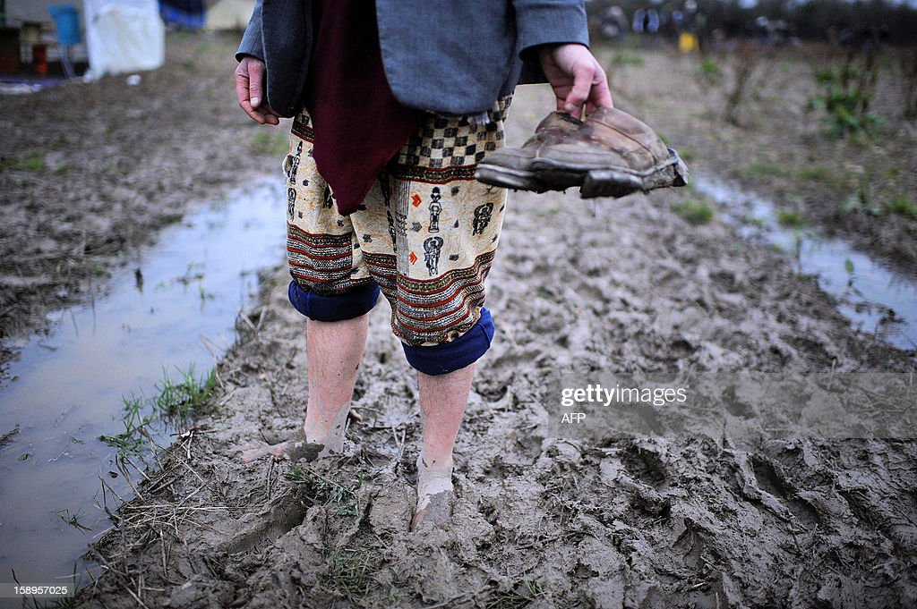 A man carries his shoes as he walks on the mud on his way to attend a music festival organized by opponents against a project of international airport, on January 4, 2013 in Notre-Dame-des-Landes, western France. The project was signed in 2010 and the international airport is scheduled to open in 2017 near the city of Nantes.