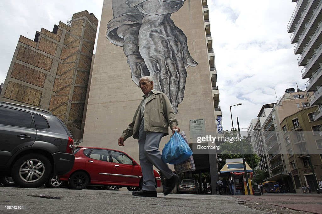 A man carries his shopping bags past a giant wall mural in Athens, Greece, on Tuesday, May 14, 2013. Greek Prime Minister Antonis Samaras said the country can beat the targets set under its 240 billion-euro ($311 billion) International Monetary Fund and euro area bailout program and return to bond markets in the first half of next year. Photographer: Kostas Tsironis/Bloomberg via Getty Images