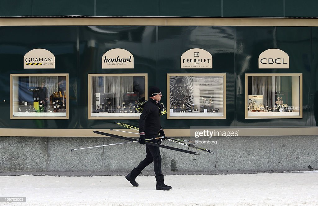 A man carries his ski's past a luxury watch store in the town of Davos, Switzerland, on Saturday, Jan. 19, 2013. Next week the business elite gather in the Swiss Alps for the 43rd annual meeting of the World Economic Forum in Davos, the five day event runs from Jan. 23-27. Photographer: Chris Ratcliffe/Bloomberg via Getty Images
