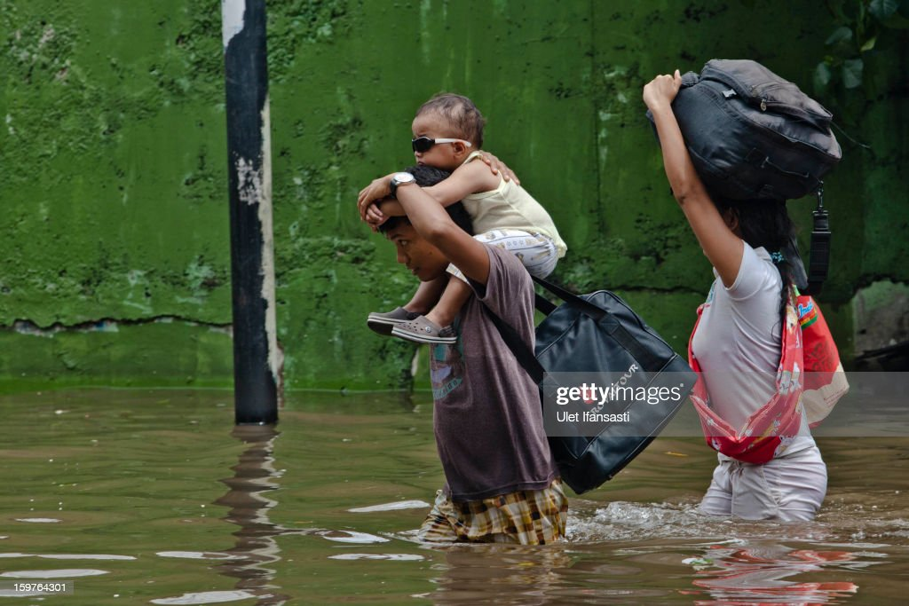 A man carries his son as he makes his way through floodwaters as major floods hit North Jakarta on January 20, 2013 in Jakarta, Indonesia. The death toll has risen to at least 21 since severe flooding struck the city on January 17. The US has offrered US$150,000 (Rp 1.44 billion) in aid.