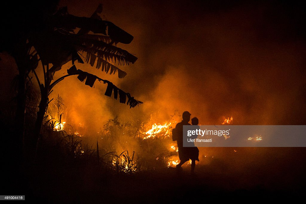 A man carries his son as he walks through the haze on the way to his house as a fire burned peatland and fields at Ogan Ilir district on October 2...