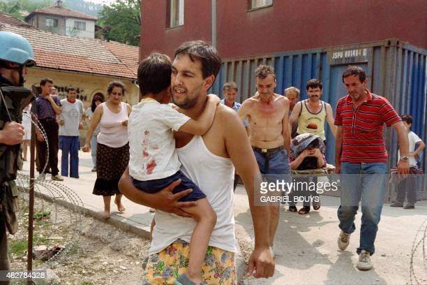 A man carries his son injured in the back by mortar shrapnel in front of a woman on a stretcher on August 08 1993 after a shell landed near a water...