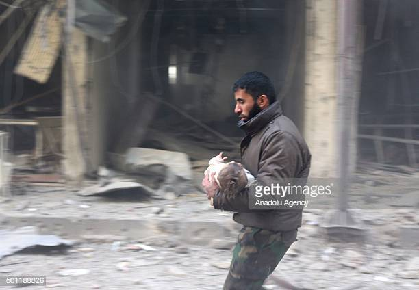 A man carries his wounded baby after the war crafts belonging to the Russian Army carried out airstrikes on oppositioncontrolled Sakba district of...