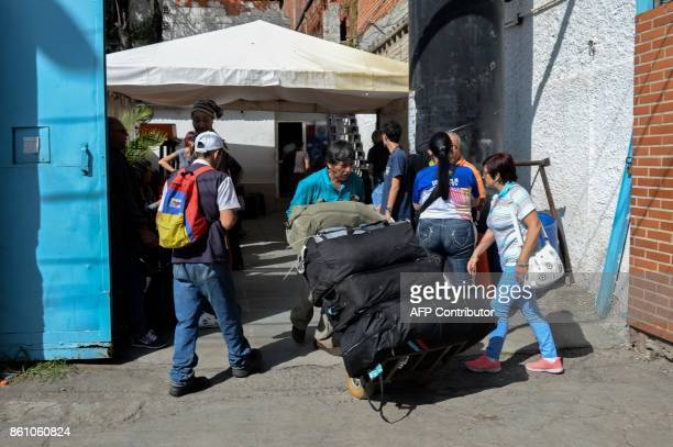 A man carries luggage of passengers at a bus terminal in Caracas on October 11 2017 as scores of disappointed Venezuelans who see no end to the...