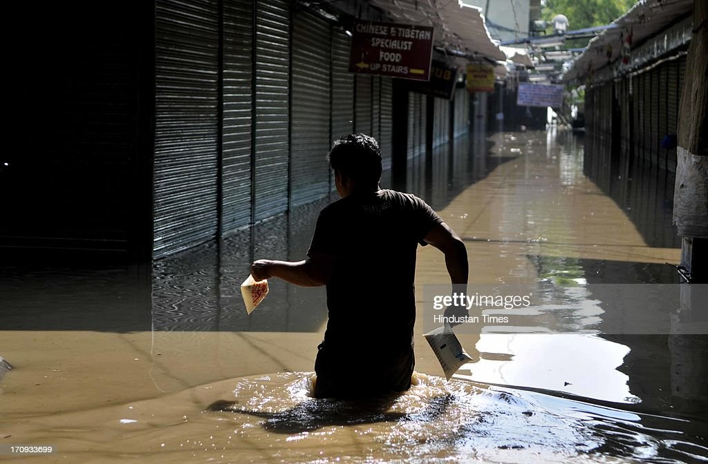 A man carries milk Ladakh monastry through the water logged lanes during flood in river Yamuna on June 20, 2013 in New Delhi, India. Low-lying areas along the Yamuna remained submerged for the second consecutive day though the water level in the river started receding today.