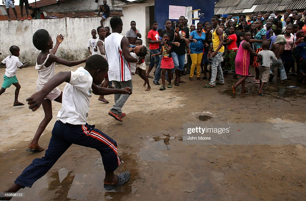 A man carries out a girl from an Ebola isolation center as a mob overruns the facility in the West Point slum on August 16 2014 in Monrovia Liberia A...