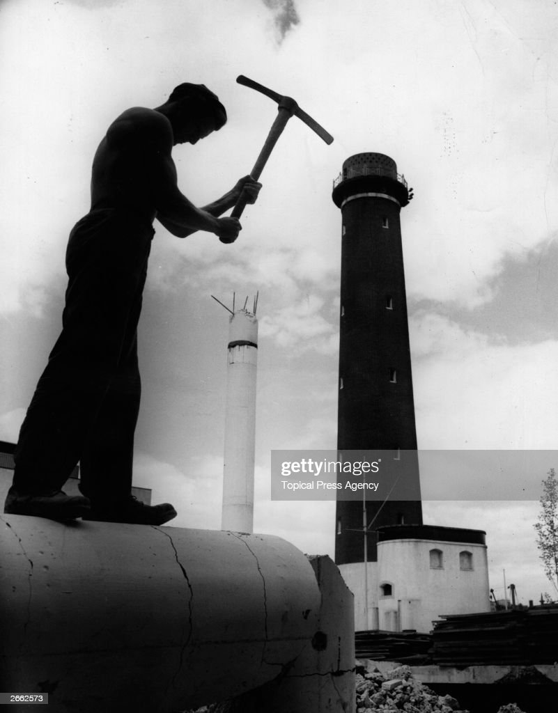 A man carries out demolition work on the Festival of Britain site, at the South Bank, London. The shot tower is in the background.