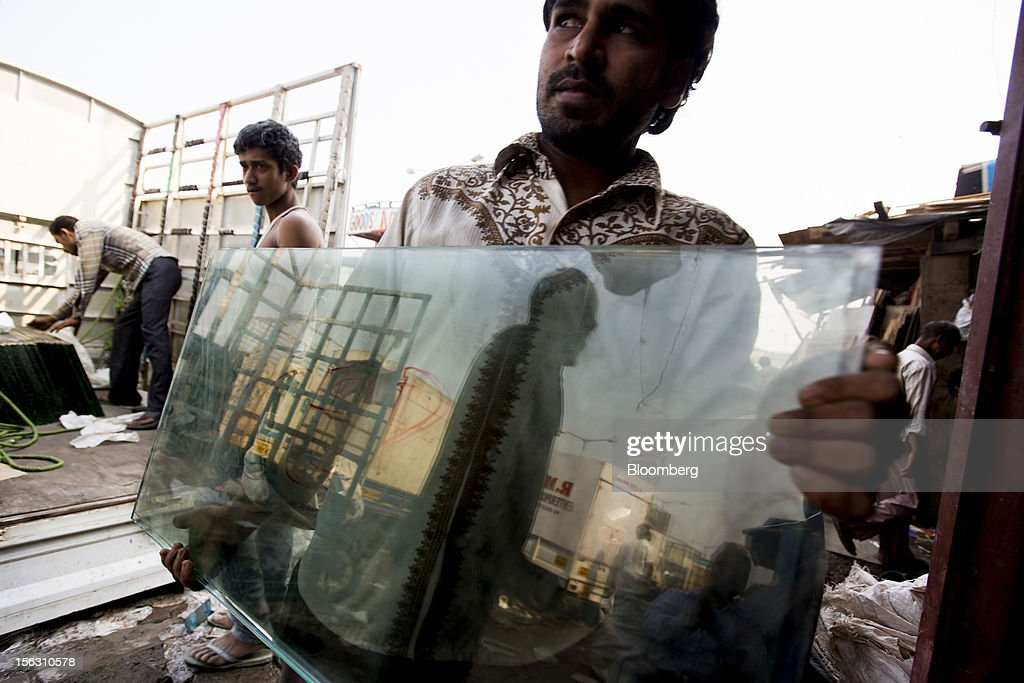A man carries panes of glass to a workshop in the Dharavi slum area of Mumbai, India, on Friday, Nov. 9, 2012. Indian industrial production unexpectedly fell in September and the trade deficit widened to a record last month as exports declined, adding to signs that Asia's third-largest economy is struggling. Photographer: Brent Lewin/Bloomberg via Getty Images