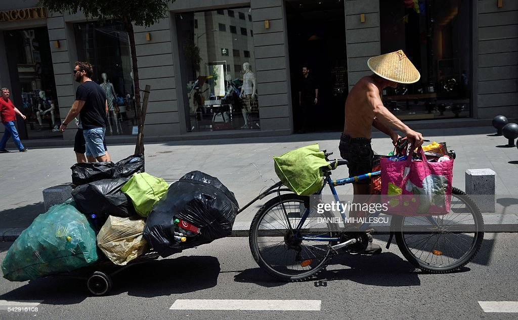 A man carries plastic bottles on his bike to be recycled in Bucharest on June 25, 2016. / AFP / DANIEL