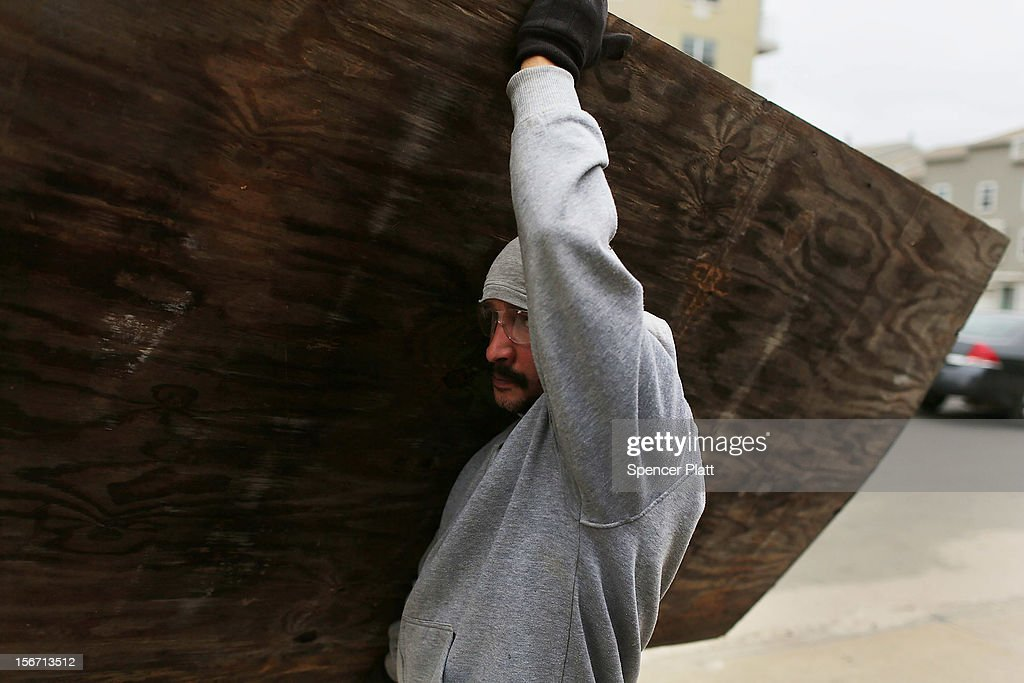 A man carries plywood in the heavily damaged Rockaway neighborhood, where a large section of the iconic boardwalk was washed away on November 19, 2012 in the Queens borough of New York City. Three weeks after Superstorm Sandy slammed into parts of New York and New Jersey, thousands are still without power and heat.