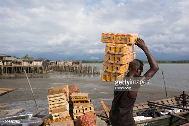 A man carries Poker brand beer to a boat bound for the El Choco region of Buenaventura Colombia on Tuesday Sept 22 2015 Buenaventura which serves as...