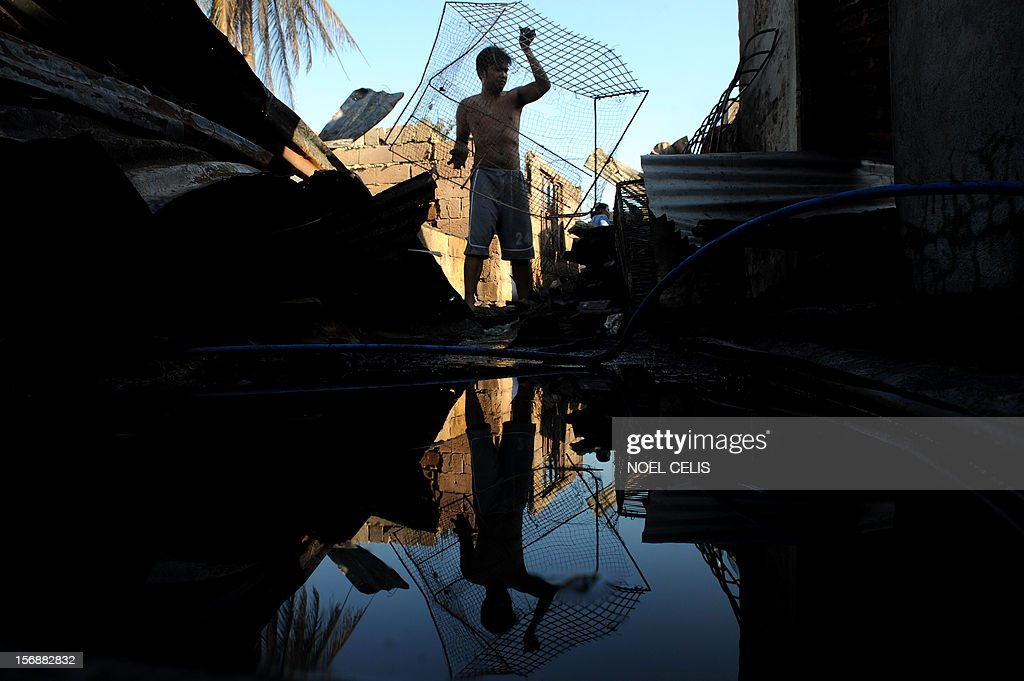 A man carries salvageable materials among the debris of burnt houses destroyed after an overnight fire razed a slum area in Manila on November 24, 2012. Three children died as a result of the fire and almost 150 were affected according to local media report.