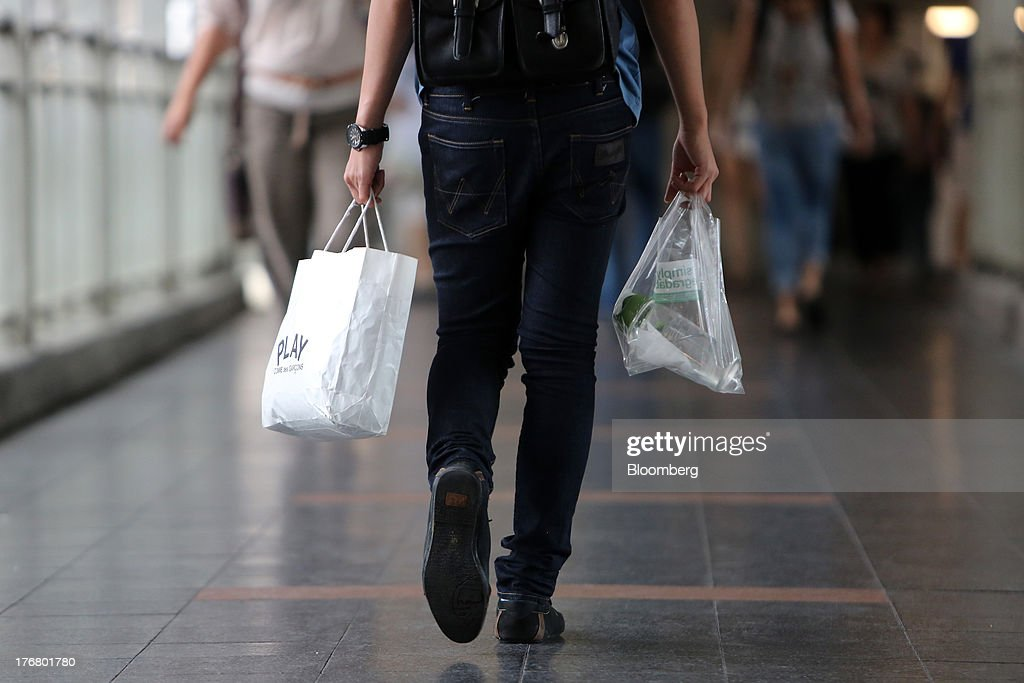 A man carries shopping bags in central Bangkok, Thailand, on Sunday, Aug. 18, 2013. Thai economic growth slowed for a second quarter as exports cooled and local demand weakened, with rising household debt restricting the scope for monetary easing. Photographer: Dario Pignatelli/Bloomberg via Getty Images