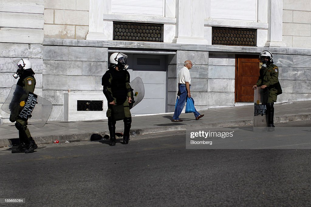 A man carries shopping bags past riot police during a general strike in Athens, Greece, on Tuesday, Nov. 6, 2012. Greece headed for a cliffhanger vote on austerity measures needed to keep the bailout on track as a 48-hour general strike began and European officials squabbled over the timing of a deal to unlock rescue funds. Photographer: Kostas Tsironis/Bloomberg via Getty Images