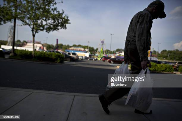A man carries shopping bags while walking out of the Marley Station Mall as the Dreamland Amusements carnival sits in the parking lot in Glen Burnie...