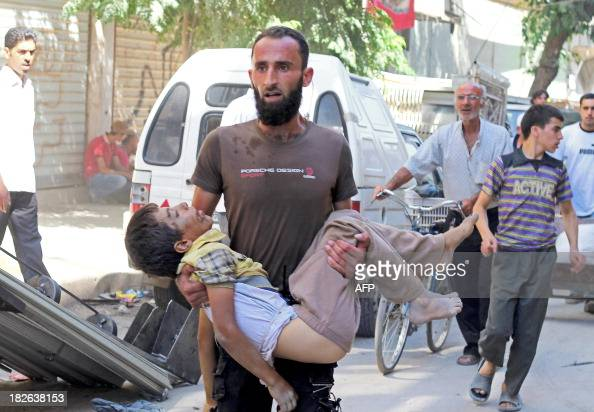 A man carries the body of a child allegedly killed by a progovernment forces sniper in the northern Syrian city of Aleppo on October 2 2013 At least...