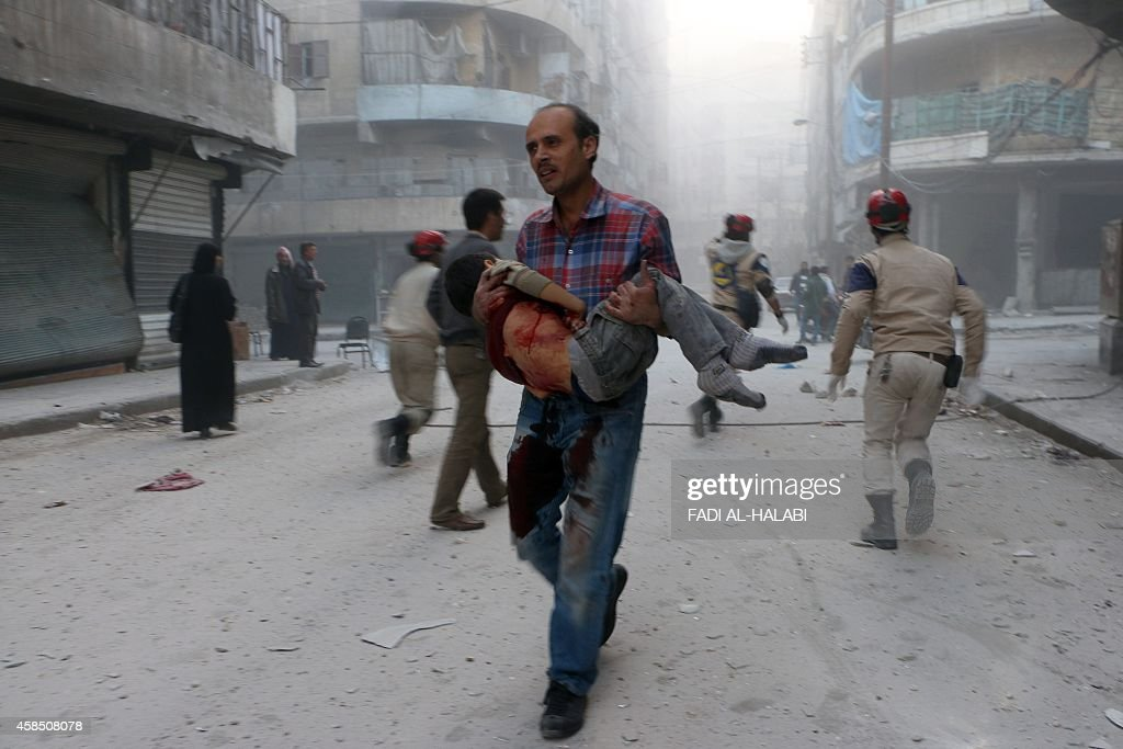 A man carries the body of his son following a reported barrel bomb attack by government forces in the AlMuasalat area in the northern Syrian city of...