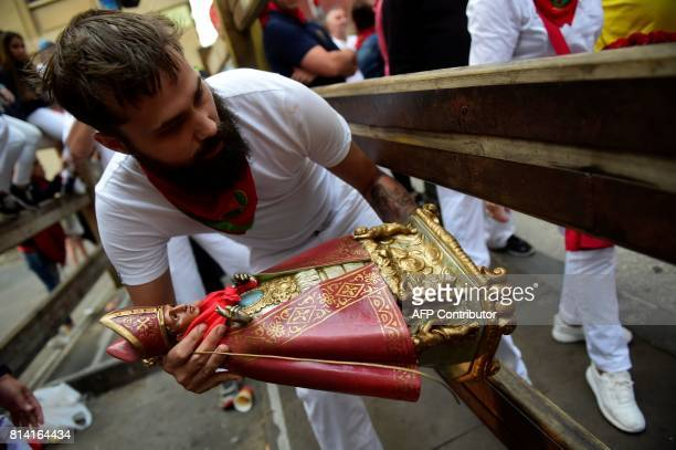 A man carries the figure of San Fermin as he waits for the Miura's fighting bulls before the eighth and last bull run of the San Fermin festival in...