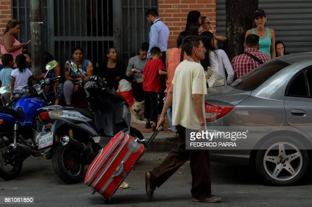 A man carries the suitcase of a passenger at a bus station in Caracas on October 11 2017 as scores of disappointed Venezuelans who see no end to the...