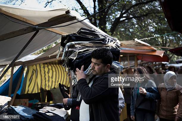 A man carries trousers at the semiweekly outdoor market at Maybachufer in Kreuzberg district on October 29 2013 in Berlin Germany According to...