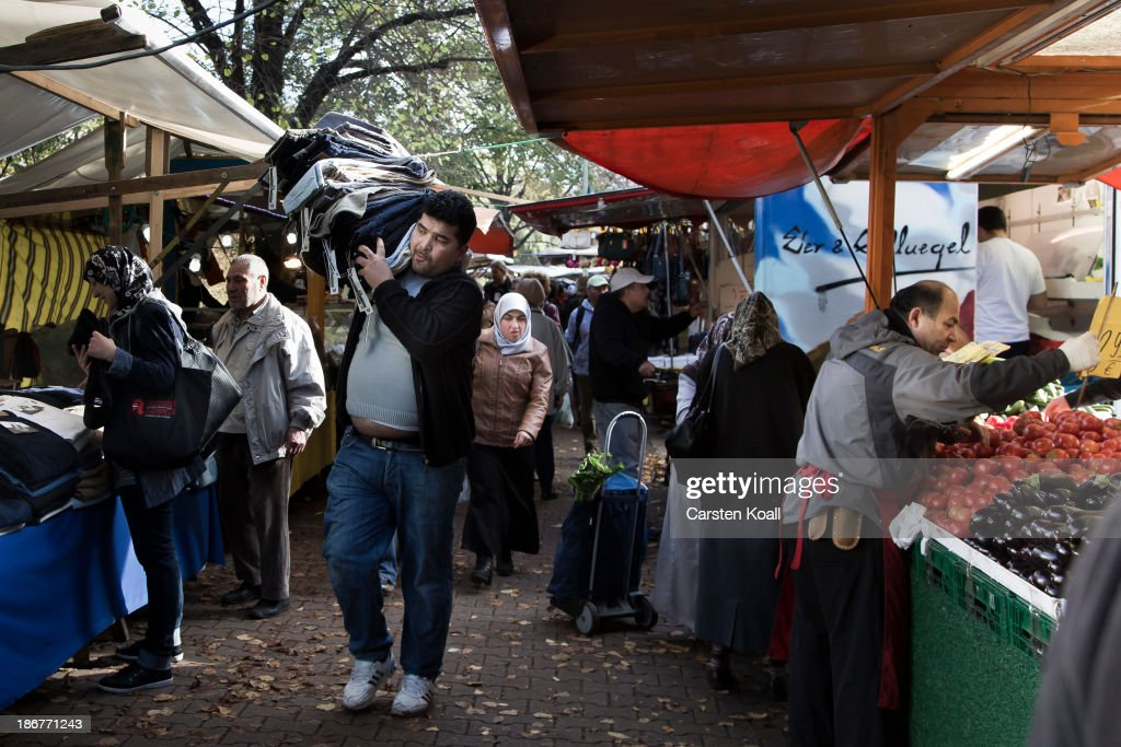 A man carries trousers at the semi-weekly outdoor market at Maybachufer in Kreuzberg district on October 29, 2013 in Berlin, Germany. According to recently published statistics, 7.2 million foreigners were living in Germany by the end of 2012, which is the highest number ever recorded. Of those 80% are from countries in the European Union, while the rest come primarily from Turkey, Russia, the former Soviet states and Arab countries.