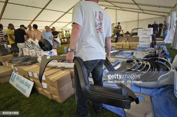 A man carries two brand new replacement wheel arches for a VW Baywindow Type 2 Transporter in the trade stands area at Vanfest festival in the Three...