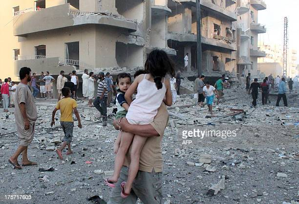 A man carries two children away from the scene of an explosion in the northern Syrian city of Raqqa early on August 7 2013 UN weapons inspectors...