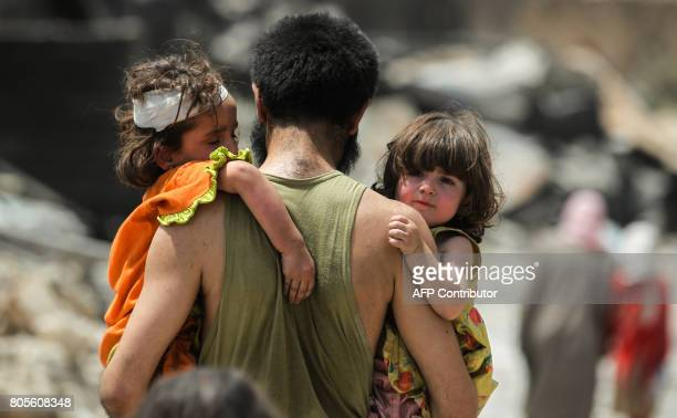 TOPSHOT A man carries two children in his arms hile fleeing from the Old City of Mosul on July 2 as Iraqi government forces continue their offensive...