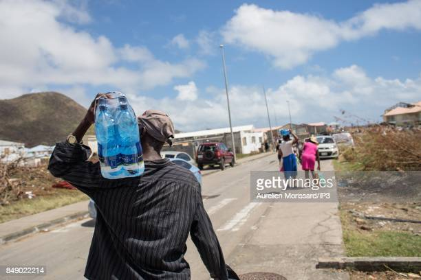 A man carries water in front of Saint Martin III's College in the Orleans neighborhood eleven days after the passage of hurricane Irma on September...