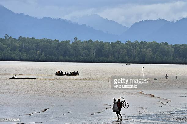 A man carring his bicycle walks next to a river in the town of Kerema Papua New Guinea on September 5 2014 AFP PHOTO / ARIS MESSINIS