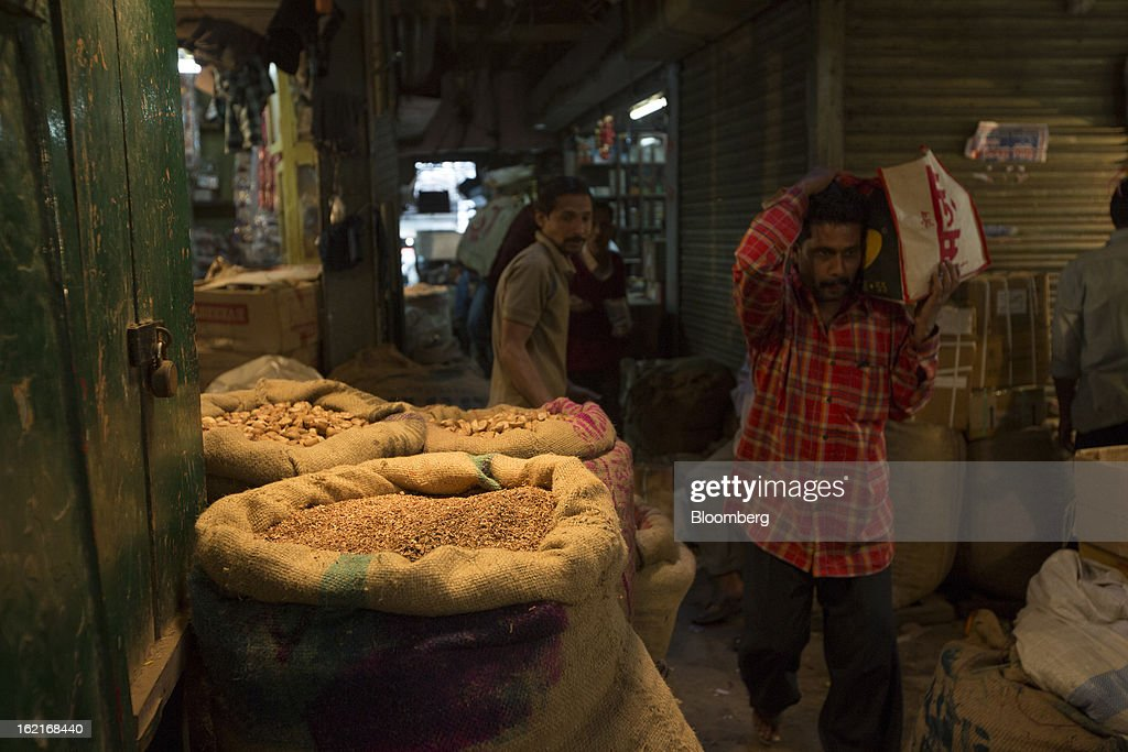 A man carrying a bag on his shoulder walks past grain displayed for sale in the Burrabazar area of Kolkata, India, on Tuesday, Feb. 19, 2013. India's slowest economic expansion in a decade is limiting profit growth at the biggest companies even as foreigners remain net buyers of the nation's stocks, according to Kotak Institutional Equities. Photographer: Brent Lewin/Bloomberg via Getty Images