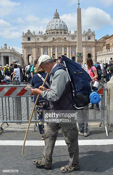 A man carrying a bagpack reads a map as he arrives at St Peter's square on April 26 2014 at the Vatican a day before the canonisation of Popes John...