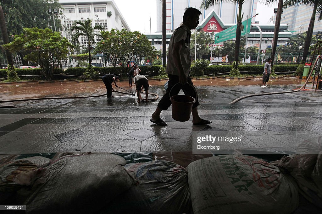 A man carrying a bucket walks past sandbags as workers pump water out of the Jalan Thamrin boulevard in central Jakarta, Indonesia, on Friday, Jan. 18, 2013. Indonesia declared a state of emergency in Jakarta as flooding brought traffic to a standstill in the city of 9.6 million people and swamped the offices of President Susilo Bambang Yudhoyono. Photograph by: Dimas Ardian/Bloomberg via Getty Images