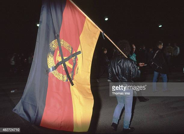 Man carrying a crossed flag of the German Democratic Republic on German Unity Day on October 03 in Berlin Germany The year 1990 marks the 25th...