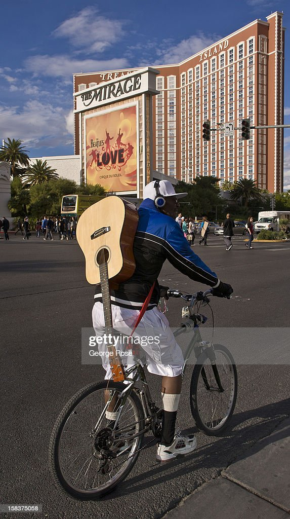 A man carrying a guitar on his back rides his bike past Treasure Island Hotel & Casino on November 18, 2012 in Las Vegas, Nevada. Tourism in America's ''Sin City'' is slowly making a comeback from the Great Recession with visitors filling the hotels, restaurants, and casinos in record numbers.