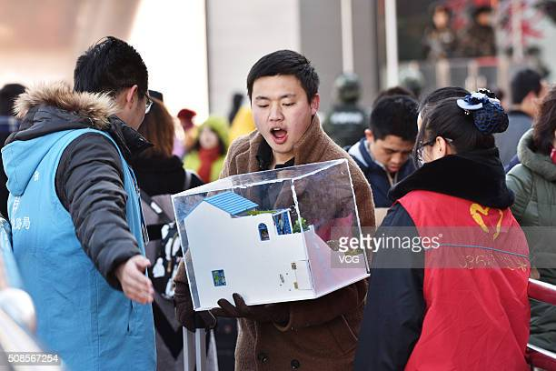 A man carrying a house model as he heads back home for the upcoming Spring Festival at Beijing West Railway Station on February 5 2016 in Beijing...