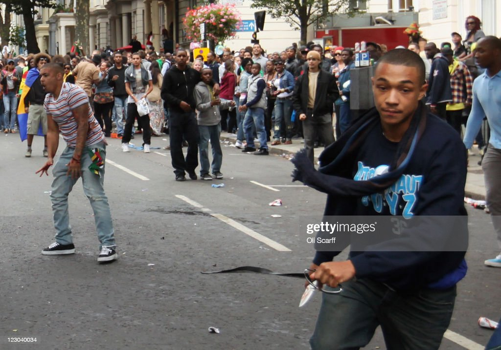 A man carrying a knife avoids being tripped by a member of the public as he runs down the road at the Notting Hill Carnival on August 29, 2011 in London, England. The annual carnival, which is the largest of its kind in Europe and is expected to attract around 1 million revellers, has taken place every August Bank Holiday since 1966.