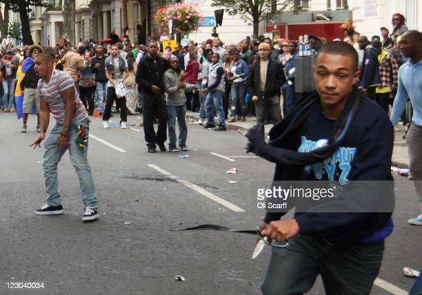 A man carrying a knife avoids being tripped by a member of the public as he runs down the road at the Notting Hill Carnival on August 29 2011 in...