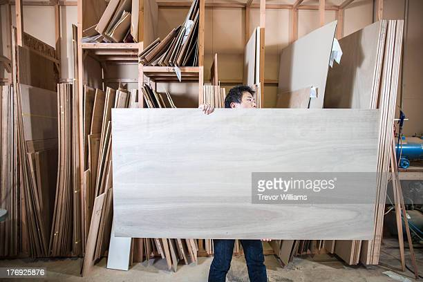 A man carrying a large board